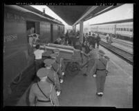 Officers saluting as men unload coffins of Korean War dead from train at Union Station in Los Angeles, Calif., 1951