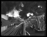 Fire fighters battling oil tank fire at Union Oil refinery in Wilmington, Calif., 1951
