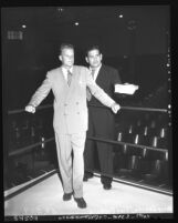 Reverend Billy Graham standing with Tiny Roebuck in ring at Hollywood Legion Stadium, Los Angeles, Calif., circa 1951