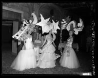 Three women in gowns and headdresses at Las Floristas Headdress Ball at the Biltmore Hotel in Los Angeles, Calif., 1952