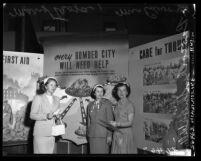 Three women standing before Alert America (civil defense) posters in Los Angeles, Calif., 1952
