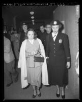 Burlesque dancer Betty Rowland, (aka Ball of Fire) being escorted by policewoman June Howard after being convicted of lewd conduct in Los Angeles, Calif., 1952