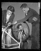 John Maggi, John Trapp and John Nicholson wearing YMCA sweaters, working on bicycle in Eagle Rock, Calif., 1953