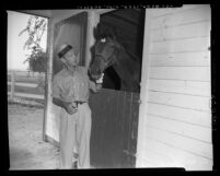 Fred Astaire with horse in stall at ranch in Los Angeles, Calif., circa 1953
