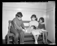 Four destitute Mexican American children sitting on bench Los Angeles, Calif., circa 1953