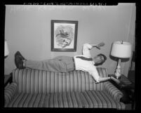 "Hank Ketcham, ""Dennis the Menace"" cartoonist, laying on back of couch, Calif., circa 1953"