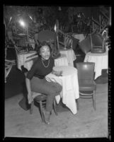 Singer Eartha Kitt, seated in empty nightclub in Los Angeles, Calif., 1953
