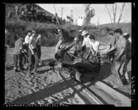 Men dragging a horse from oil sump near Slauson Ave and Sepulveda Blvd. in Los Angeles, Calif., 1953