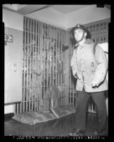 Fireman walking past crowded jail cell during prisoner's riot at Los Angeles County Jail, Calif., 1953