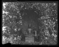 Buddha statue framed by vines at Los Angeles Mission Gardens