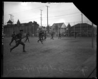 ROTC cadets running drills at Polytechnic High School in Los Angeles, Calif. with houses and spectators in background, circa 1920