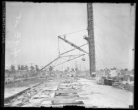 Workmen watching as crane lifts materials during construction of Ninth Street Bridge-viaduct in Los Angeles, Calif., circa 1925