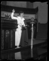 Aimee Semple McPherson speaking in front of microphone at Angelus Temple, circa 1923