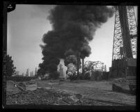 Two oil wells burning side by side at Santa Fe Springs, Calif. oil field in 1928
