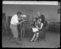 Cameraman filming close up of Anita Page talking into a telegraphone with Rufus B. Von KleinSmid behind her