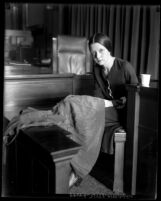 Eunice Pringle on the witness stand examining a dress during Alexander Pantages rape trial