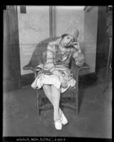Eunice Pringle sitting in a wicker chair with eyes closed and head leaning on hand
