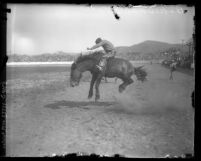 Cowboy riding a bucking bronco at the Baker Ranch Rodeo Saugus, Calif., circa 1926