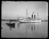 Side view of the steamship Harvard in Los Angeles Harbor with tugboat in front, circa 1921