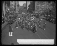 Shriner's band parading down street with buildings, pedestrians and automobiles in background in Los Angeles, Calif. circa 1927