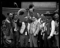 Undersheriff Gene Biscailuz, wearing fezz, standing with cowboy escort and Indians from New Mexico at train station in Los Angeles, Calif., 1925