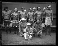 Indians from New Mexico in traditional clothing, holding rattles upon arrival at train station for Shriner convention in Los Angeles, Calif., 1925