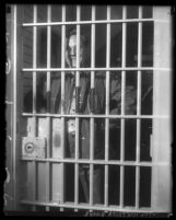 Reverend Robert Shuler with hands on hips, standing in jail cell in Los Angeles, Calif., 1930