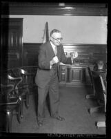 Attorney William E. Simpson standing alone in courtroom clenching both fists in Los Angeles, Calif., circa 1931