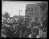 University of Southern California graduation ceremony, graduates and faculty surrounding stage with unveiled Trojan Statue, 1930