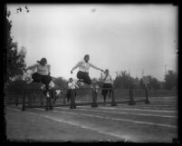 Five women athletes in bloomers and middy blouses running hurdles in Los Angeles, Calif., circa 1920