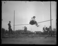 Woman high-jumper, in bloomers and middy blouse, attempting to clear the bar in Los Angeles, Calif., circa 1920