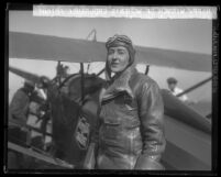 Bobbi Trout in flight suit standing beside her plane at Mines Field after setting women's endurance record, Los Angeles, Calif., 1929