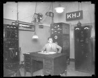 Radio engineer Ernest G. Underwood sitting at desk of his KHJ broadcasting station in Inglewood, Calif., 1927