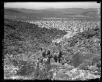 Sheriffs digging in rocky terrain with onlookers surrounding them during search for James P. Watson's murder victim in Sugarloaf Canyon, Calif., 1920