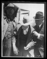 Copy of a photograph of James P. Watson being escorted by two sheriffs, Calif., 1920