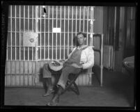 Charles Wesley Way dressed in overalls, sitting in front of jail cell after his arrest for threatening to shoot oil workers in Los Angeles, Calif., 1925