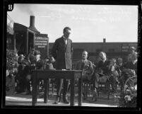 Sylvester L. Weaver Sr.,standing on outdoor stage speaking to the Los Angeles Commerce Club, circa 1926