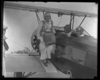 Edith Weber wearing parachute pack, standing on the wing of airplane with two men in pilot seats, Calif., circa 1931