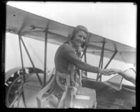Mary Wiggins, wearing parachute pack and smiling as she climbs onto plane in Los Angeles, Calif., 1931