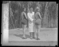 Dr. Charles E. Wood standing between two contestants in the National Chiropractic Association's perfect back contest in Los Angeles, Calif., 1927