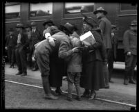 At train station, a soldier in uniform with arm around woman and leaned over kissing a boy in Los Angeles, Calif., circa 1914