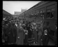 Crowd on platform watching as train arrives loaded with soldiers, leaning out of the windows waving in Los Angeles, Calif., circa 1914