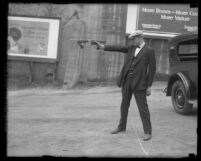 Plain-clothed policeman Oscar Bayer standing while aiming gun with one hand, Los Angeles, Calif., circa 1925