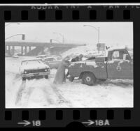 People pushing stalled truck off Magic Mountain Parkway during snow storm in Valencia, Calif., 1974