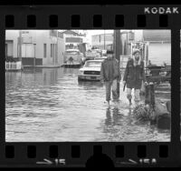 Couple wading through flooded streets in Newport Beach, Calif., 1974