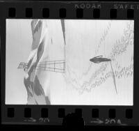 Ronald Erb walking up snow covered hill towards utility pole near Gorman, Calif., 1974