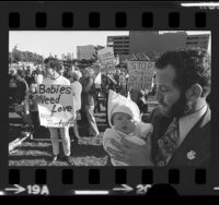 """Man holding baby amongst Pro-life demonstrators with signs, one reading """"Babies Need Love Not Torture"""" in Los Angeles, Calif., 1974"""