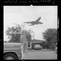 Esther F. Hall and granddaughter watching 747 jetliner, on route to LAX, fly over their home in Los Angeles, Calif., 1973