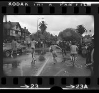 Three male streakers running and cycling through rain at USC as crowd watches, Los Angeles, Calif., 1974
