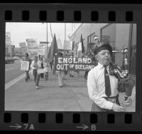 "Bagpiper leading demonstrators with banner reading ""England out of Ireland"" to British Consulate in Los Angeles, 1974"